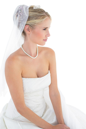 off shoulder: Young bride thinking while sitting against white background