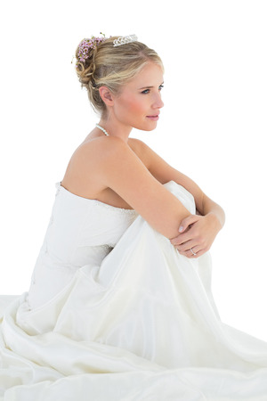 off the shoulder: Full length side view of thoughtful bride hugging knees over white background Stock Photo