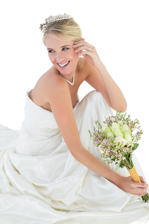 off the shoulder: Happy bride holding bouquet while looking away over white background