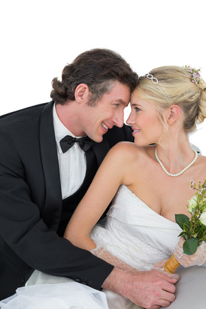 attractive bride and groom with head to head against white