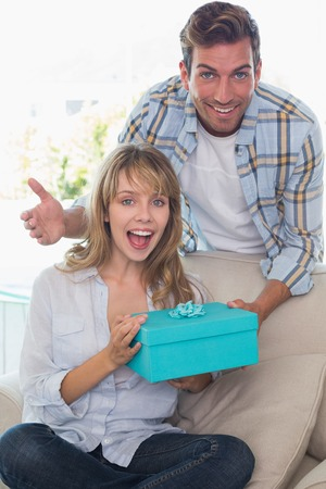 Young man surprising woman with a gift in the living room at home photo