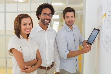 Portrait of smiling business people with digital tablet in the office photo