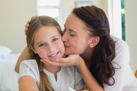 Loving mother kissing daughter at home Stock Photo