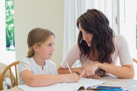child studying: Young woman helping daughter in homework at table in house