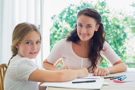 child studying: Portrait of smiling mother and daughter drawing at table in house