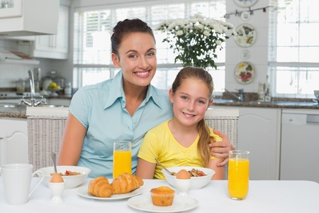 Portrait of happy mother and daughter sitting at breakfast table photo