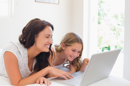 Happy woman with daughter using laptop in bed at home photo