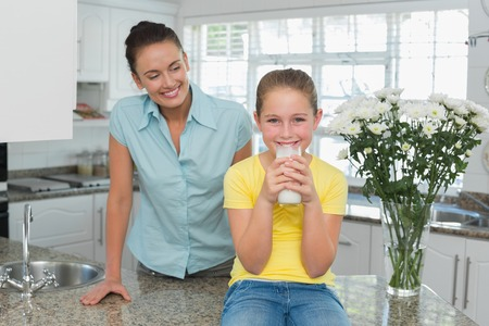 Beautiful mother looking at girl drinking milk in kitchen photo
