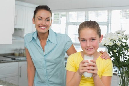 Portrait of cute girl having milk while mother standing by in kitchen photo