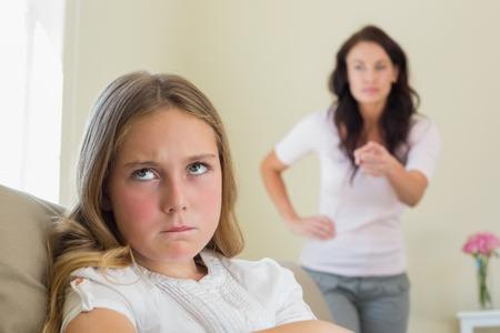 Boos meisje met moeder uitbrander haar op de achtergrond thuis Stockfoto