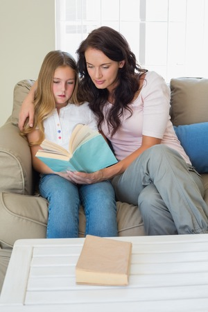 Little girl and mother reading novel together on sofa at home photo
