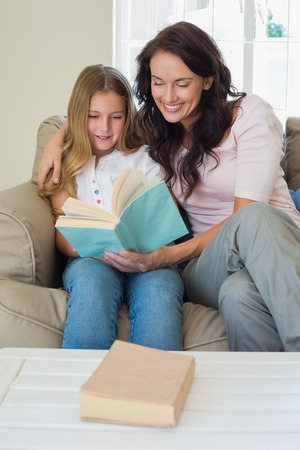 Girl and mother reading novel together on sofa at home photo