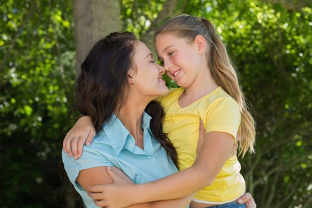 rubbing noses: Smiling mother and daughter rubbing noses in park Stock Photo