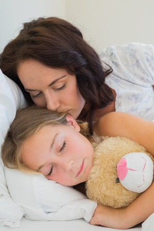 Beautiful mother kissing sleeping daughter in bed at home photo