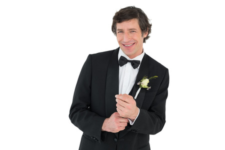 Portrait of happy man adjusting cuff links before wedding over white background Stock Photo - 28042748
