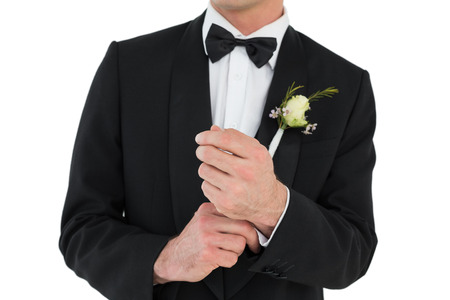 Mid section of groom adjusting cuff links before wedding over white background photo