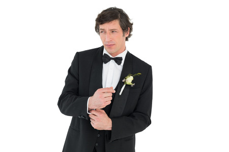 Groom in tuxedo adjusting cuff link on white background photo