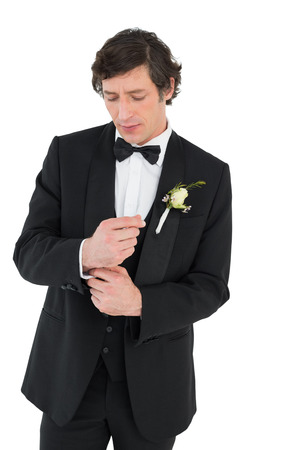 Handsome groom in tuxedo adjusting cuff link on white background photo