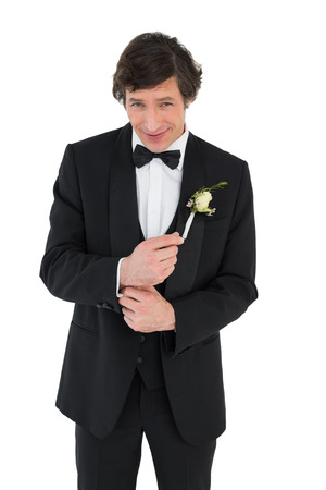Portrait of smiling groom in tuxedo getting ready over white background photo