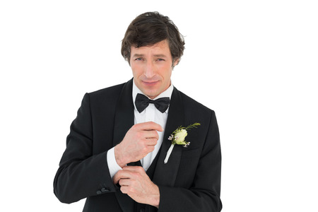Portrait of handsome groom in tuxedo getting ready over white background photo