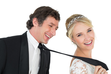 Portrait of attractive bride pulling tie of groom over white background photo