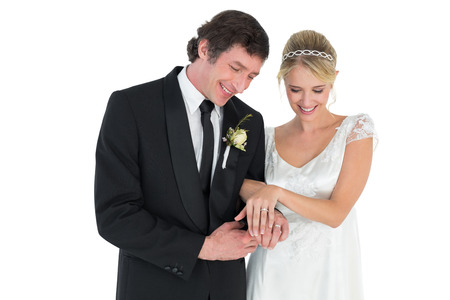 Happy newlywed couple looking at wedding rings on white background photo