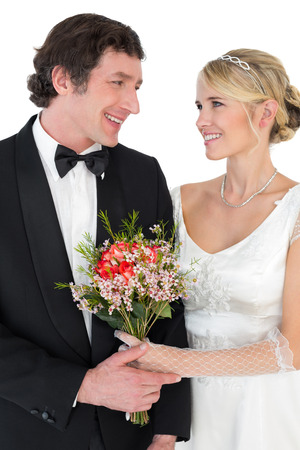 Smiling bride and groom with flower bouquet looking at each other over white background photo