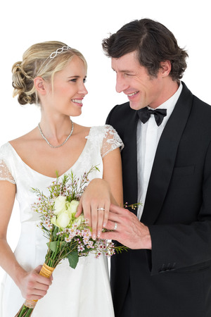 Happy bride and groom wearing wedding rings while looking at each other over white background photo
