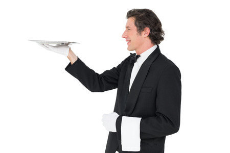 Smiling waiter carrying tray against white background photo