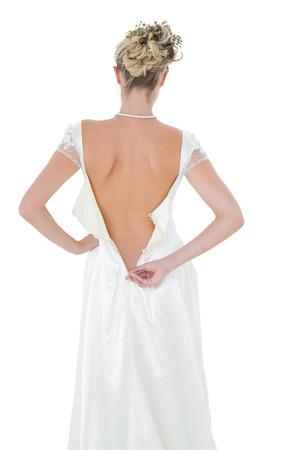 vistiendose: Vista posterior de la novia vestirse m�s de fondo blanco