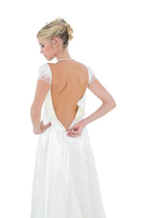 vistiendose: Vista posterior de la novia vestirse contra el fondo blanco