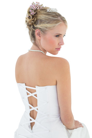 off the shoulder: Rear view of young bride in off shoulder dress looking away against white background