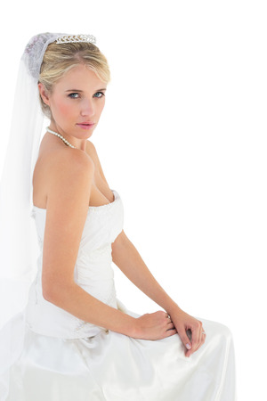 sensuous: Portrait of sensuous bride in off shoulder dress sitting against white background