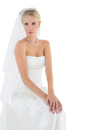 off the shoulder: Thoughtful bride in off shoulder dress sitting against white background