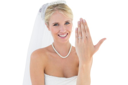 off the shoulder: Portrait of happy bride showing wedding ring over white background