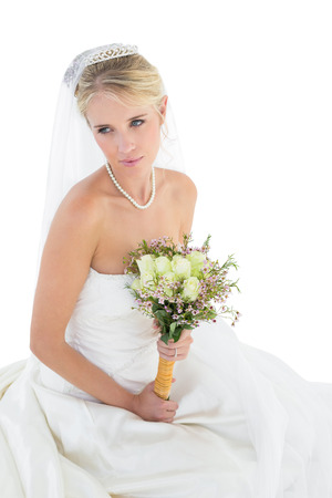 off shoulder: Thoughtful young bride holding rose bouquet over white background Stock Photo