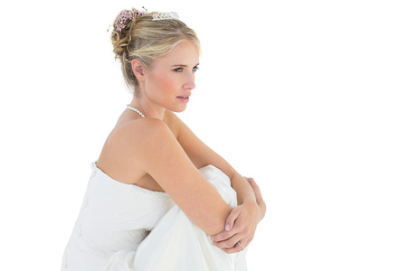 hugging knees: Side view of thoughtful bride hugging knees over white background Stock Photo