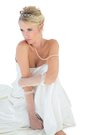 sensuous: Thoughtful sensuous bride sitting over white background