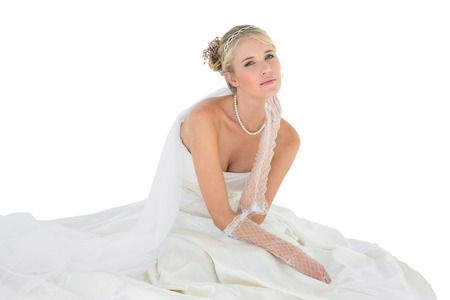 sensuous: Portrait of sensuous woman in wedding dress sitting over white background