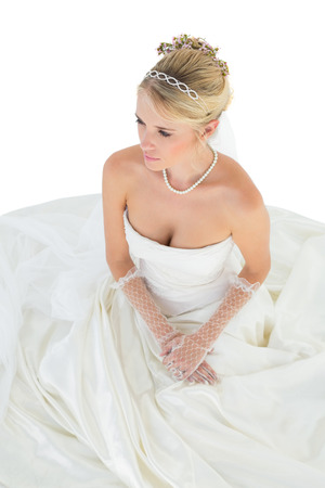 off shoulder: High angle view of young bride thinking while sitting over white background