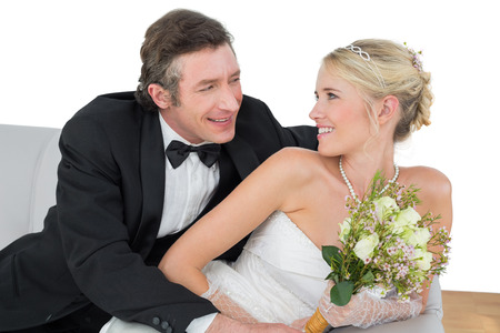 Happy bride and groom looking at each other while sitting on sofa at home photo