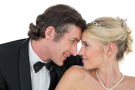 Smiling bride and groom with head to head against white background photo