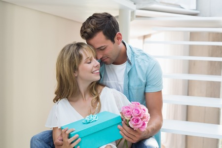 Loving young couple with flowers and gift box sitting on stairs at home photo