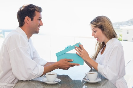 Side view of a young man giving happy woman gift box at home Stock Photo