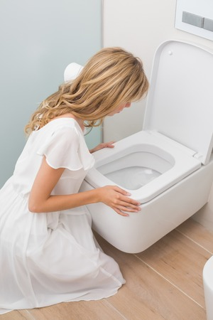 High angle view of a young woman about to vomit into a toilet photo