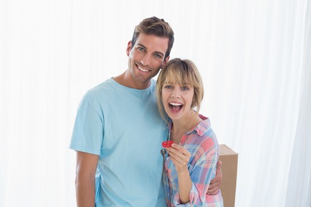 Portrait of a happy young couple holding new house key photo