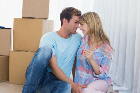 Happy loving young couple holding new house key against cardboard boxes photo