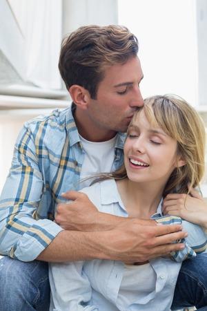 Loving young man embracing and kissing woman at home photo