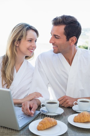 Relaxed young couple using laptop on breakfast table at home photo