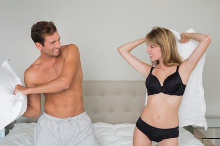 Cheerful semi nude young couple pillow fighting in bed at home Stock Photo - 28044389